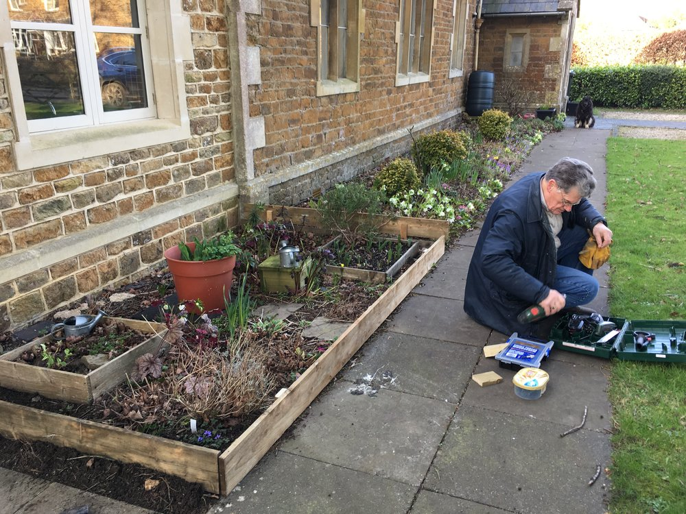 Eric, one of our volunteers, prepares to insert new edging to the Rainbows' bed at the Baptist Hall