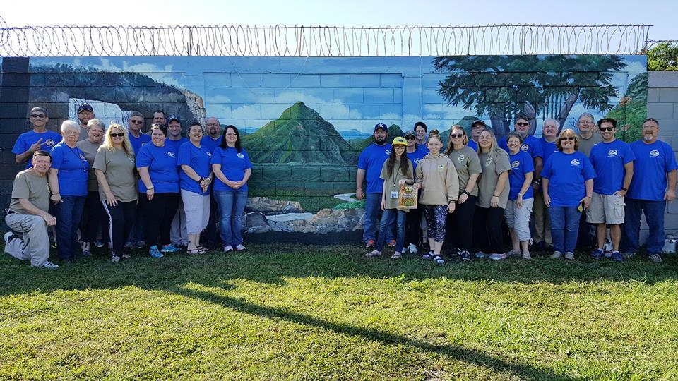 The combined teams in front of a mural one of the team members painted over his two-week visit.