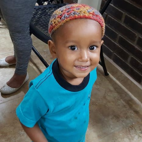Boy waiting in the clinic with a hat made by one of the team members