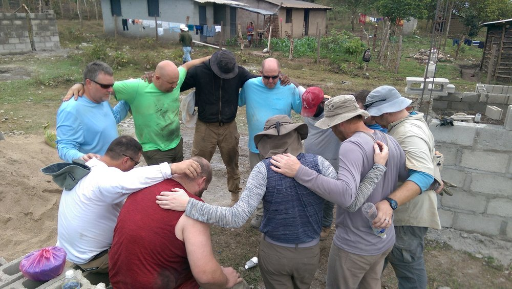Praying over the houses and the families that will live in them on the last day of construction.