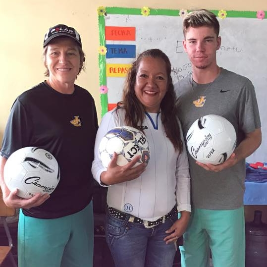 Team members donating soccer balls to the school director