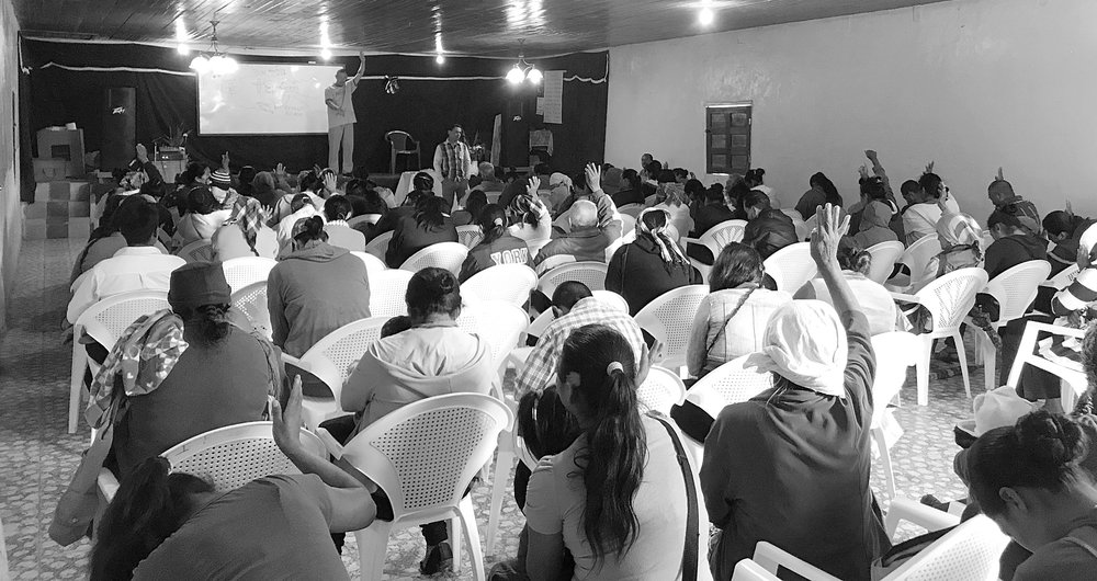 Pastor Derek praying the prayer of salvation with some of those (raising their hands) who decided to make the choice to follow Christ.