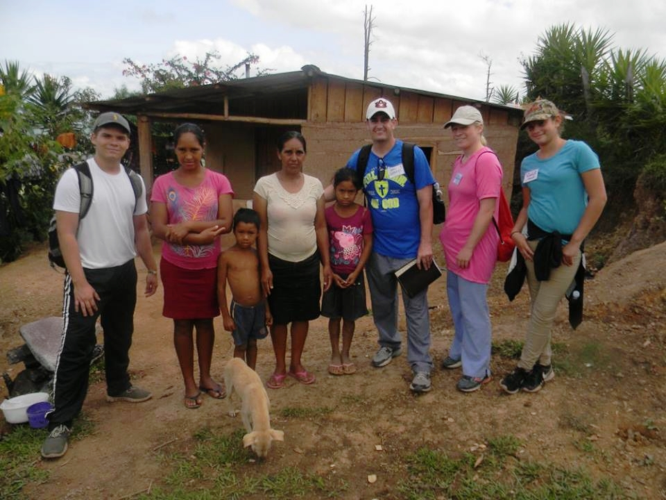 Some team members and one of HBDM's translators with a family after a home visit in the mountains.