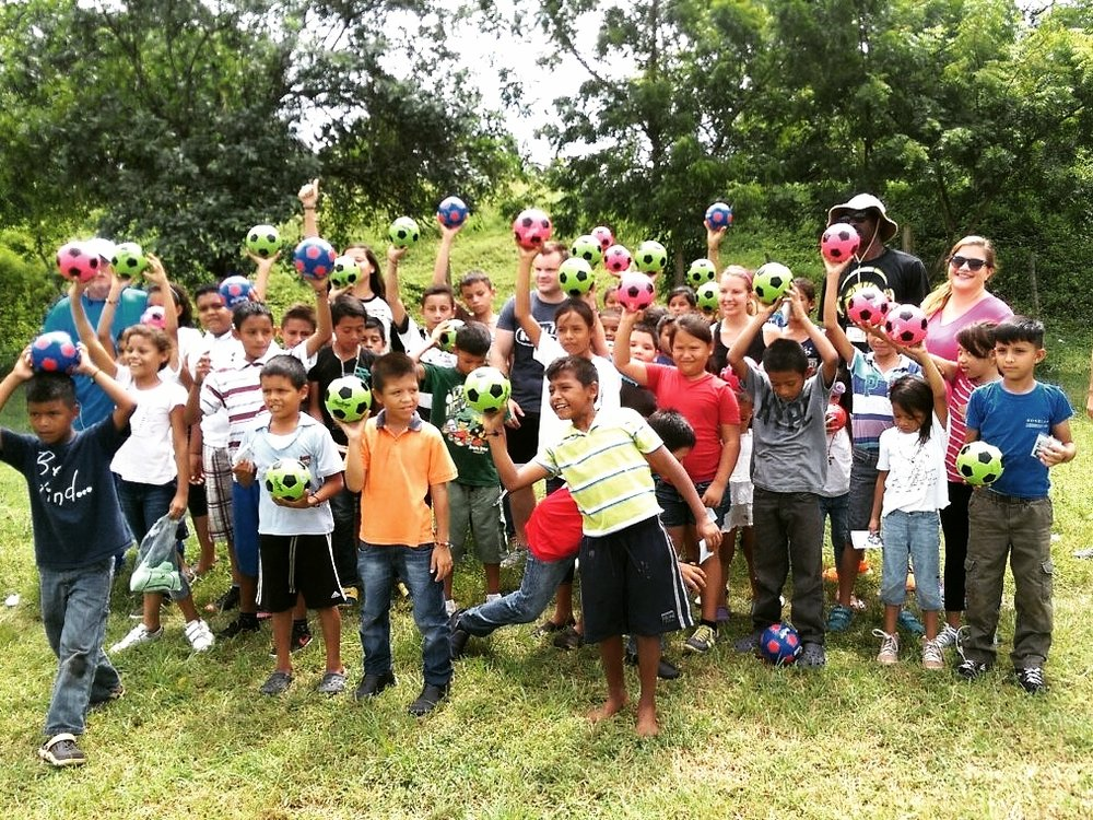 The morning group on the last day of soccer camp receiving the soccer balls that the team brought for them.