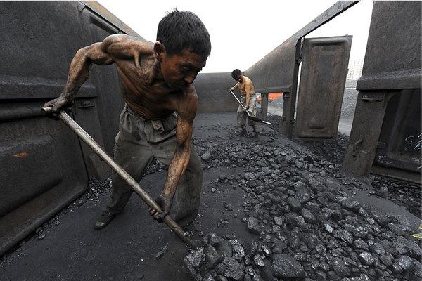 Trabalhadores descarregam carvão em um depósito ao longo da estação ferroviária de Hefei, na província de Anhui. Outobro de 2000.