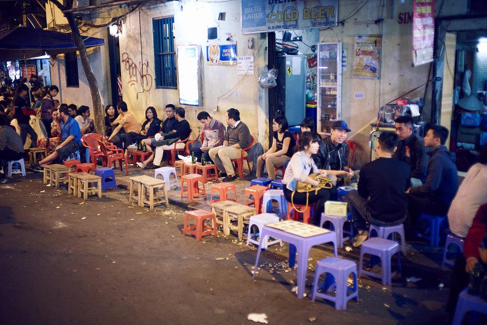 Fim de tarde típico em Hanói, dezenas de pessoas acocoradas em baixos banquinhos plásticos que são espalhados ao longo da rua por dezenas de bares.