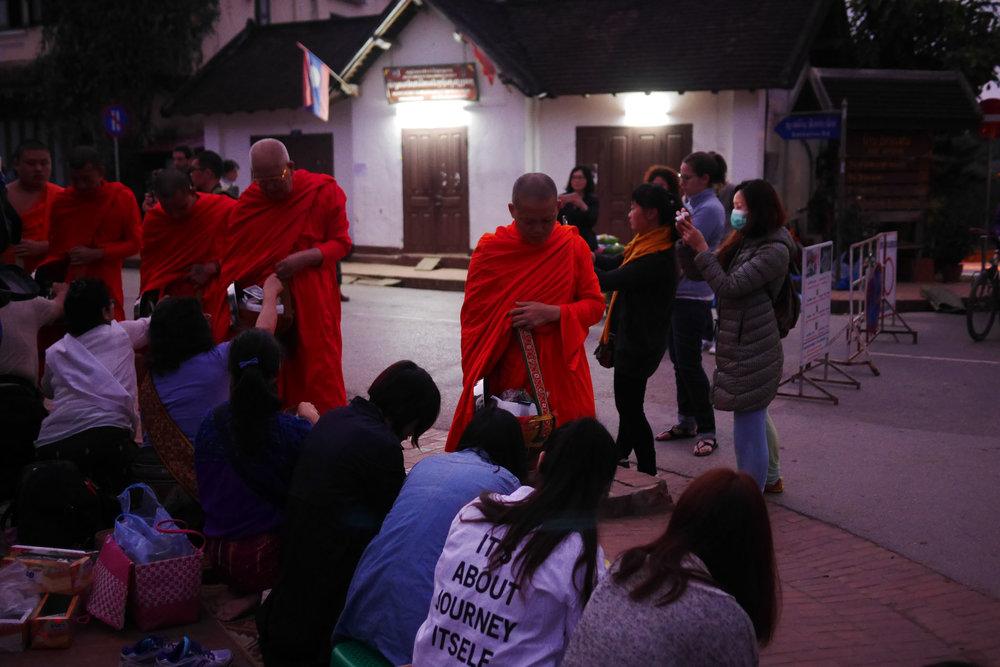 Em busca da selfie perfeita, turistas perseguem monges de câmera em punho pela avenida principal