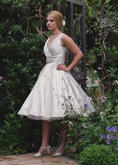 Lilianna  -Tea-length Italian silk, pleats in the surplice neckline through to the full skirt.  More>