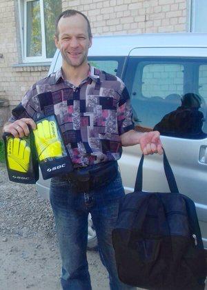 Ungdomsledaren Raivis tar emot en väska med lagtröjor och målvaktshandskar som skänkts från Hudiksvall.  Foto: Elga Racene