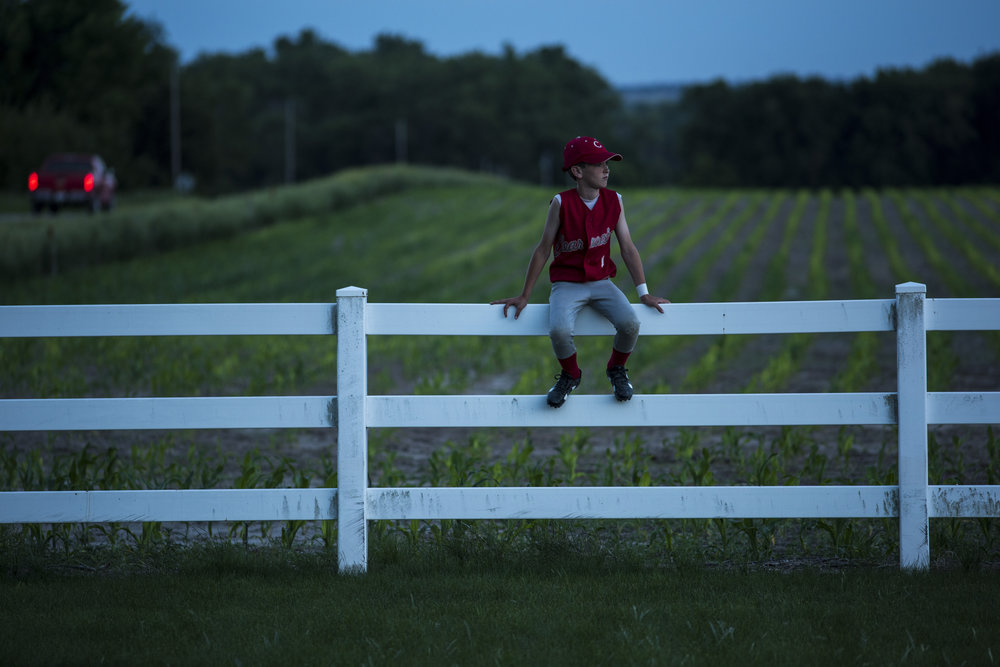 Daley Bearinger sits on the cemetery fence. The land behind him was farmed by his great, great grandparents.