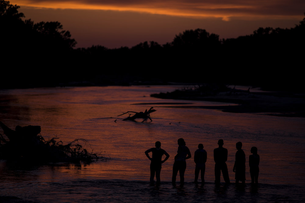 A few of the Kester great grandchildren watch the sun set over the Elkhorn River after a family picnic.