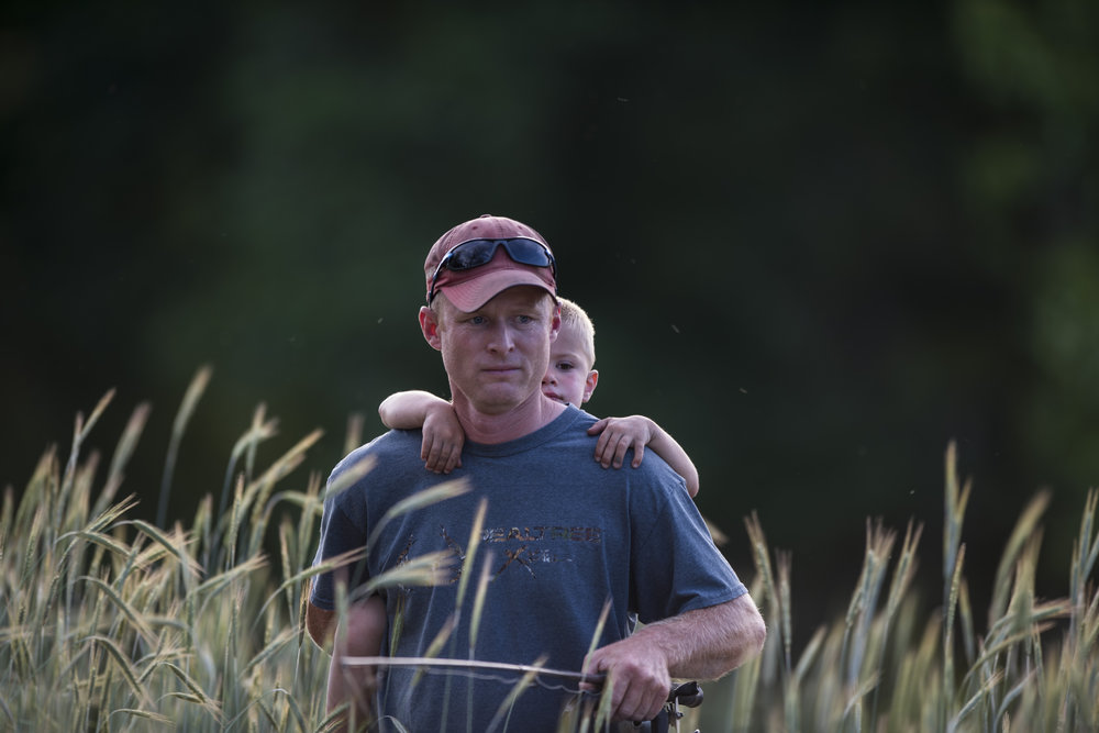 Dana Kester carries his son Trigg on his back through the weeds by the river. The two went fishing together after a family picnic.
