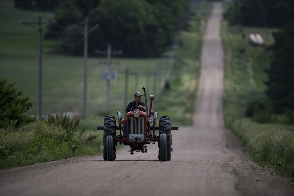 "Bob Kester drives an old tractor up a dirt road. Bob is ""retired"" but still manages to work everyday.  ""I don't like being cooped up and stuff,"" Bob said. ""No matter what the weather is I'd rather be outside and working."""