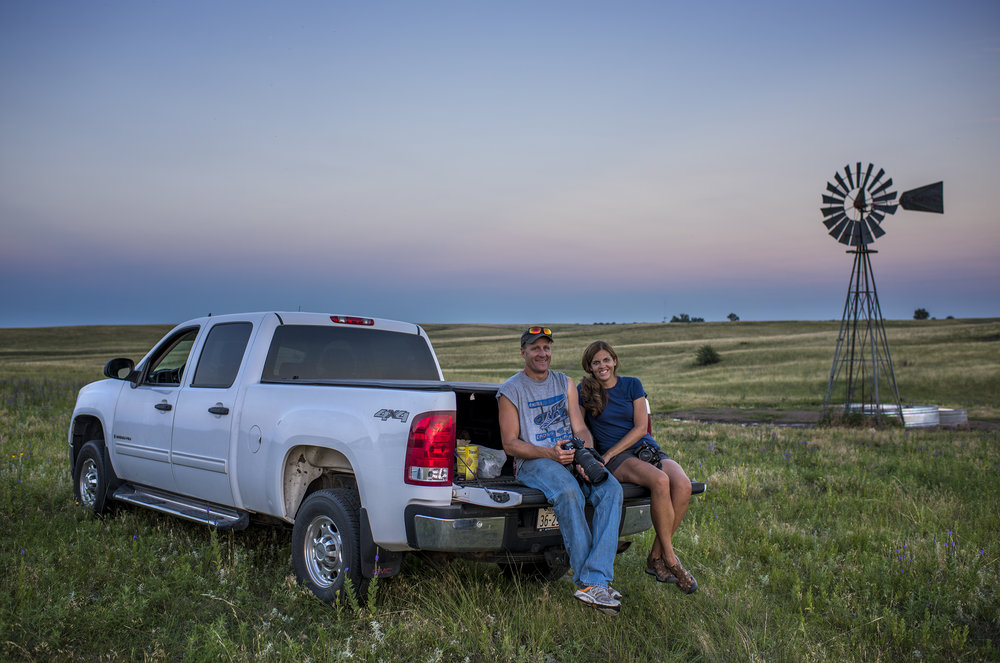 "Kevin and Katie Morrow in the tailgate of their truck on a friend's farm in Holt County, NE. That windmill with the broken blade made several appearances in our ""Nebraska Skies"" video."
