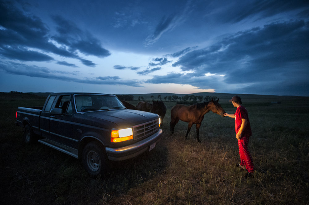 Brad feeds horses just before a thunderstorm broke out at dusk.