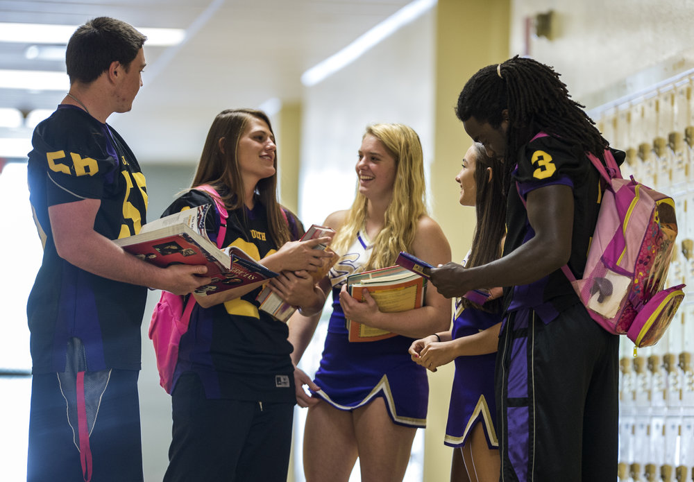 Erin and Alex talk to friends in the hallway of South Plantation High School.