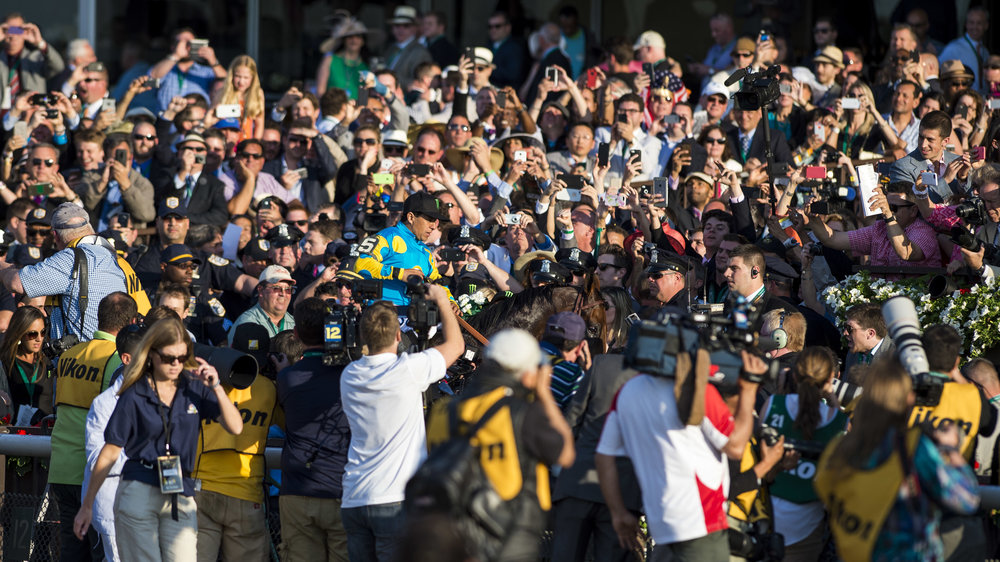 Jockey Victor Espinoza makes his way through a swarm of people to the winner's circle atop American Pharoah after winning the Belmont Stakes.