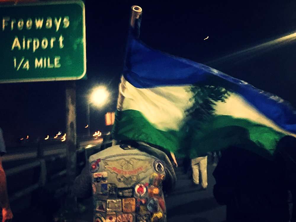 Protester marches down Interstate 84, waving the Cascadian flag.   https://www.cascadianow.org