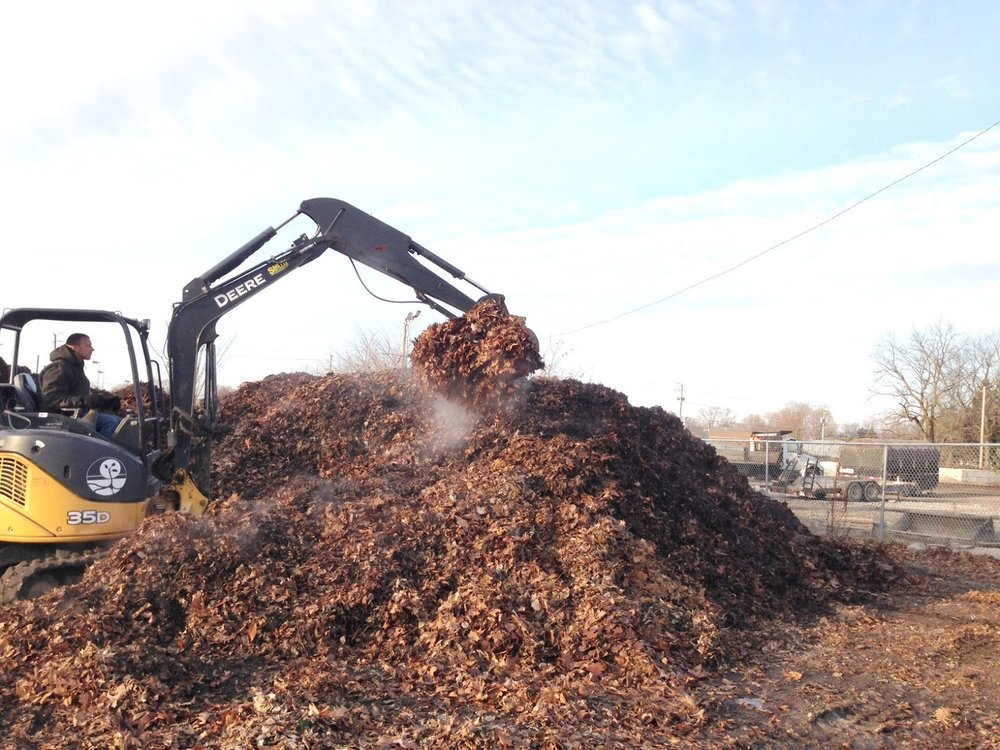 One of our maintenance staff using a mini excavator to turn the leaf compost pile