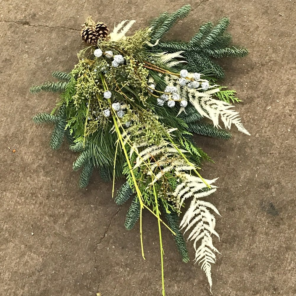 Bleached fern fronds add unique texture to this door swag made by the staff at Welch.