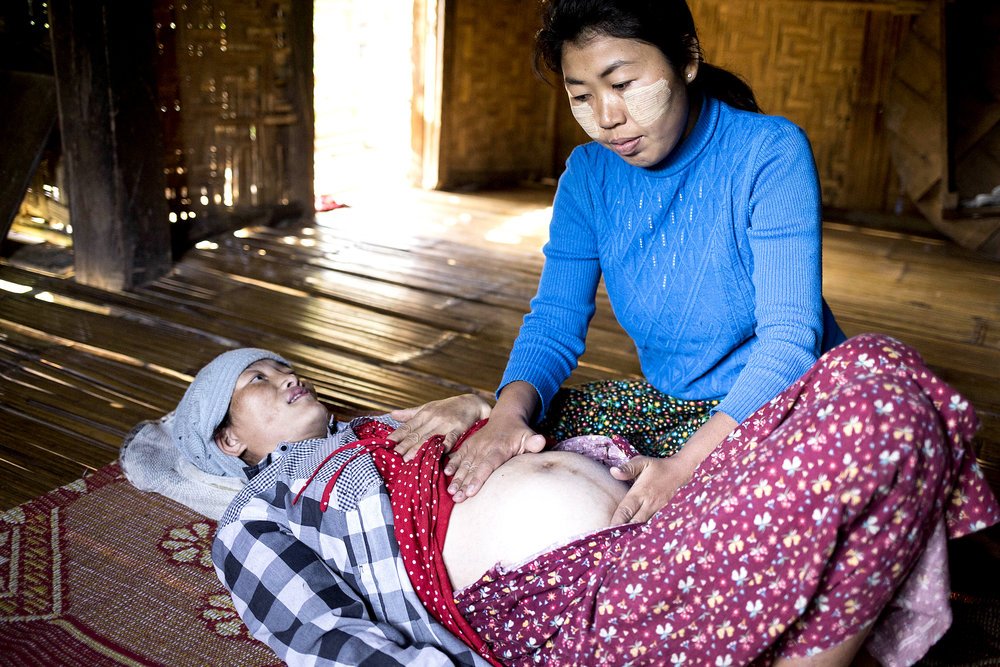 Burmese midwife assisting during a labor and delivery.