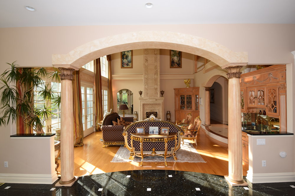 View from kitchen to Great Room with arched entry and 2 roman fluted columns