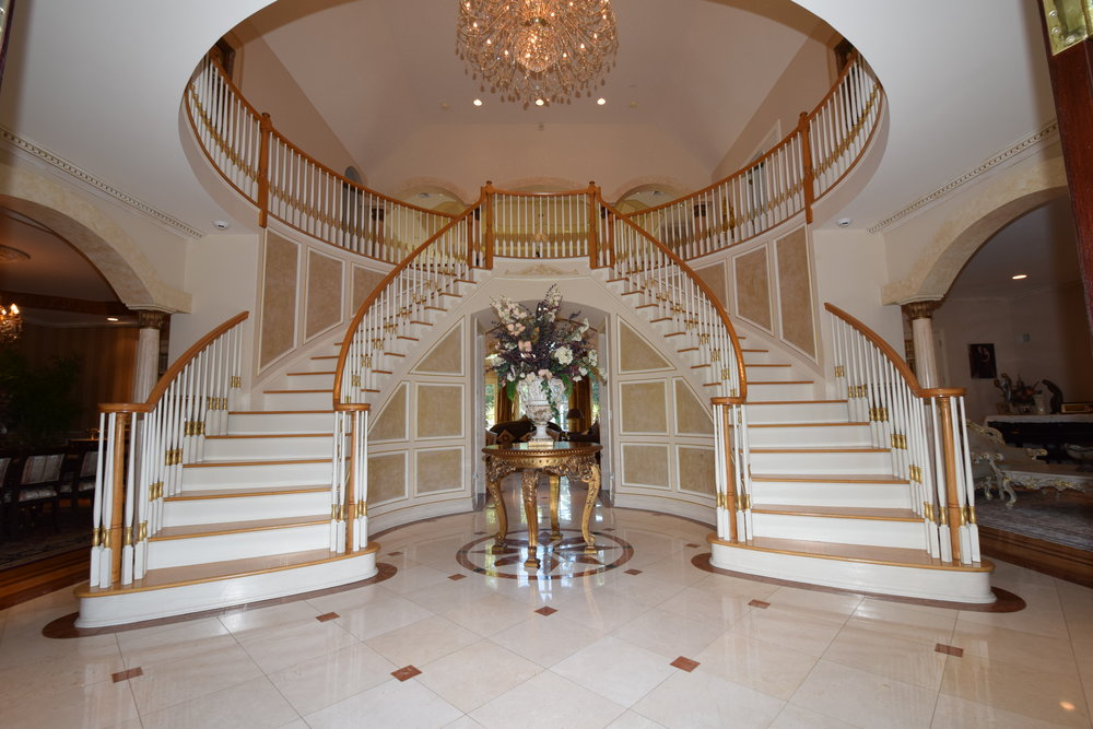 Two story high Foyer with Dramatic wrap around butterfly staircase with circular banisters, circular tray ceiling with custom textured paint