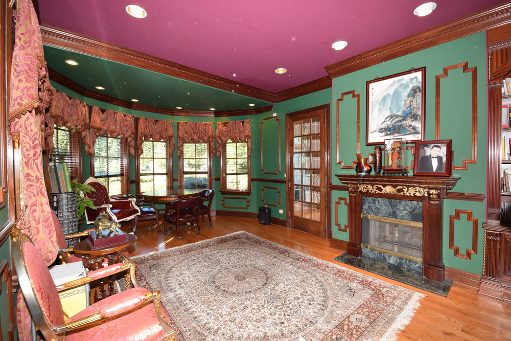 Library with custom cherry fireplace with marble surround and cherry mantle built by Old World Craftsman who also built the front door and front door window