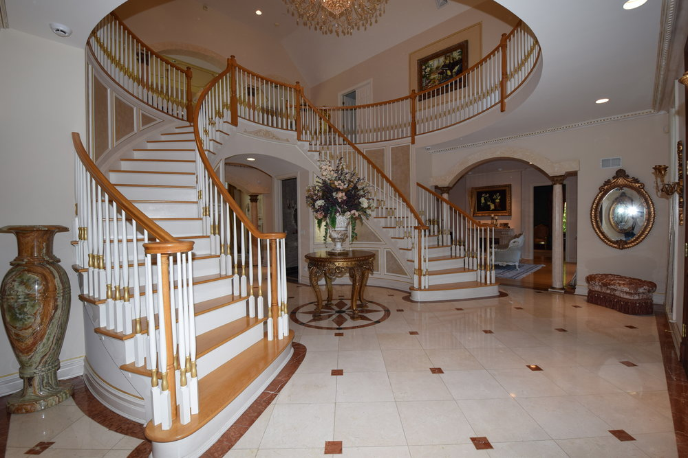 Foyer with wrap around butterfly staircase, wainscoting, picture boxes