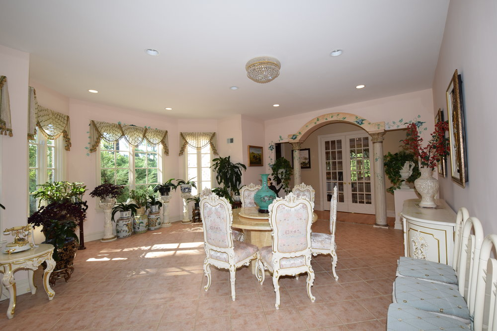 Conservatory with two roman columns with arched design with entry leading into living room, Italian custom tiled floors