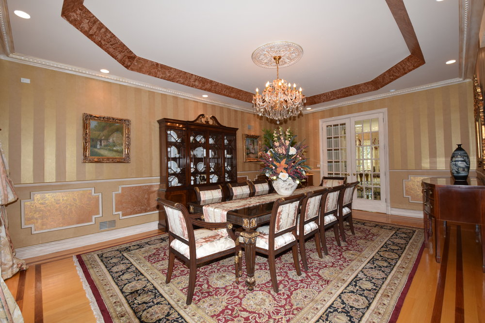 Formal dining room with hardwood floors with cherry inlay, custom chair railing, picture boxes, French door entry to kitchen/breakfast room