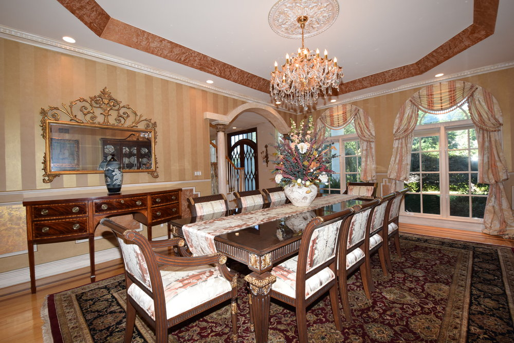 Formal dining room with tray ceiling with Venetian ceiling and walls with custom painting, two floor to ceiling palladium windows