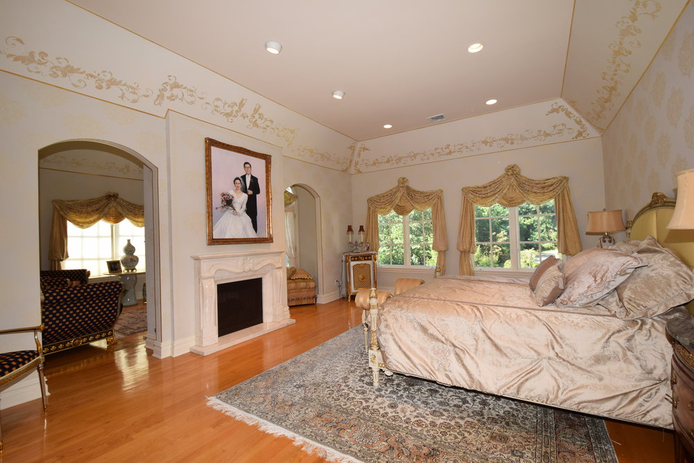 Master Bedroom with double door entry, marble fireplace, tray ceiling, and two walk in closets
