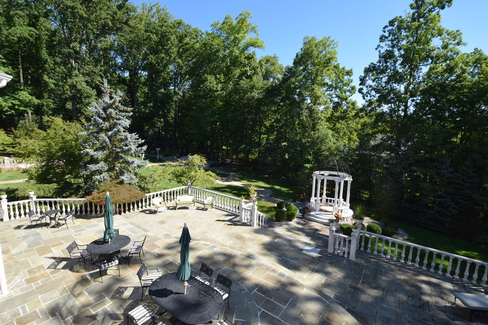 Approximately 80x40 stone patio with Italian balusters overlooking gazebo, Koi pond with waterfall and bridge