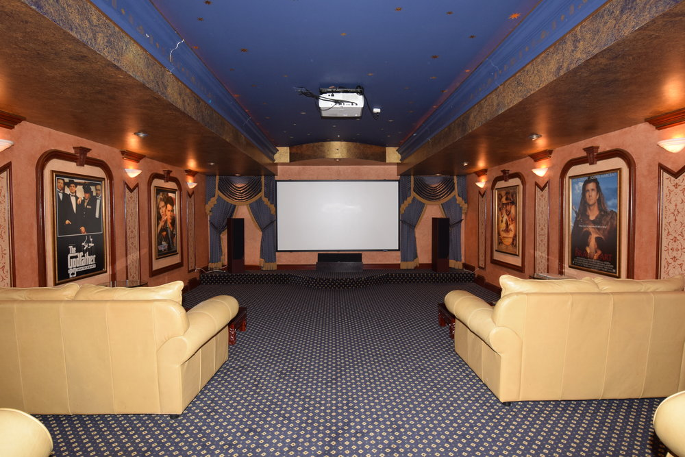 Theatre room with custom detailed cherry wood trim and design with cherry door entry
