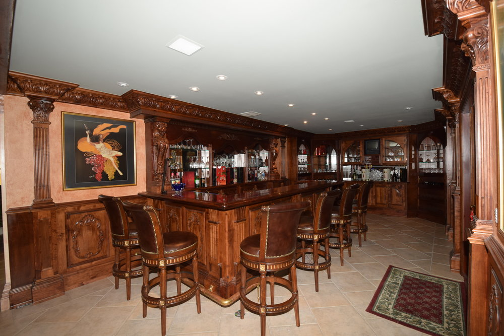 Bar featuring custom cherry cabinets, bar counter, wine cooler, refrigerators, brass sink, cherry detail through out