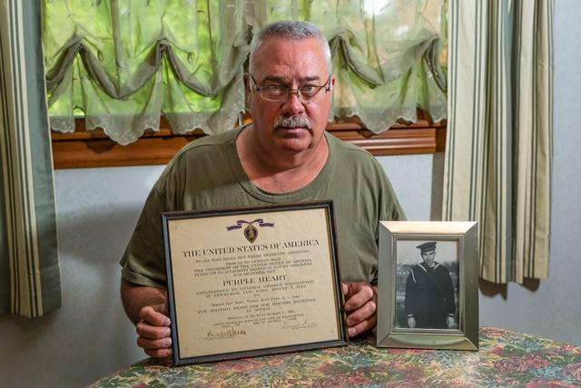 Ken Schultz, the nephew of Pearl Harbor casualty Kenneth Jayne, holds the Purple Heart his uncle was awarded posthumously in 1942.