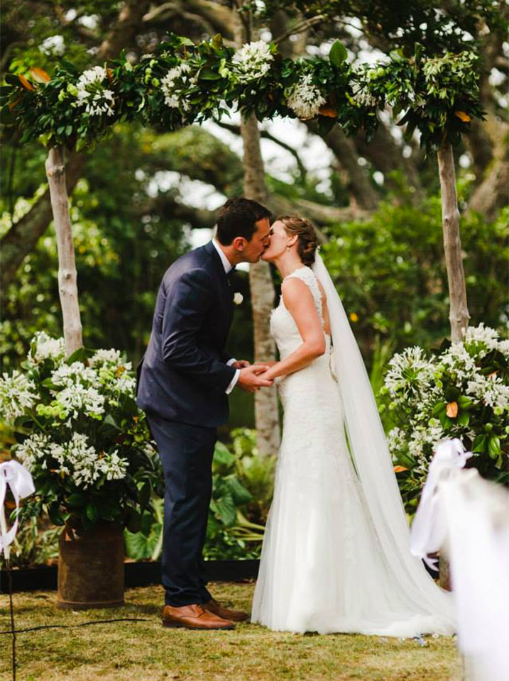 Couple kiss under arch decorated with flowers by Wildflowers Coromandel