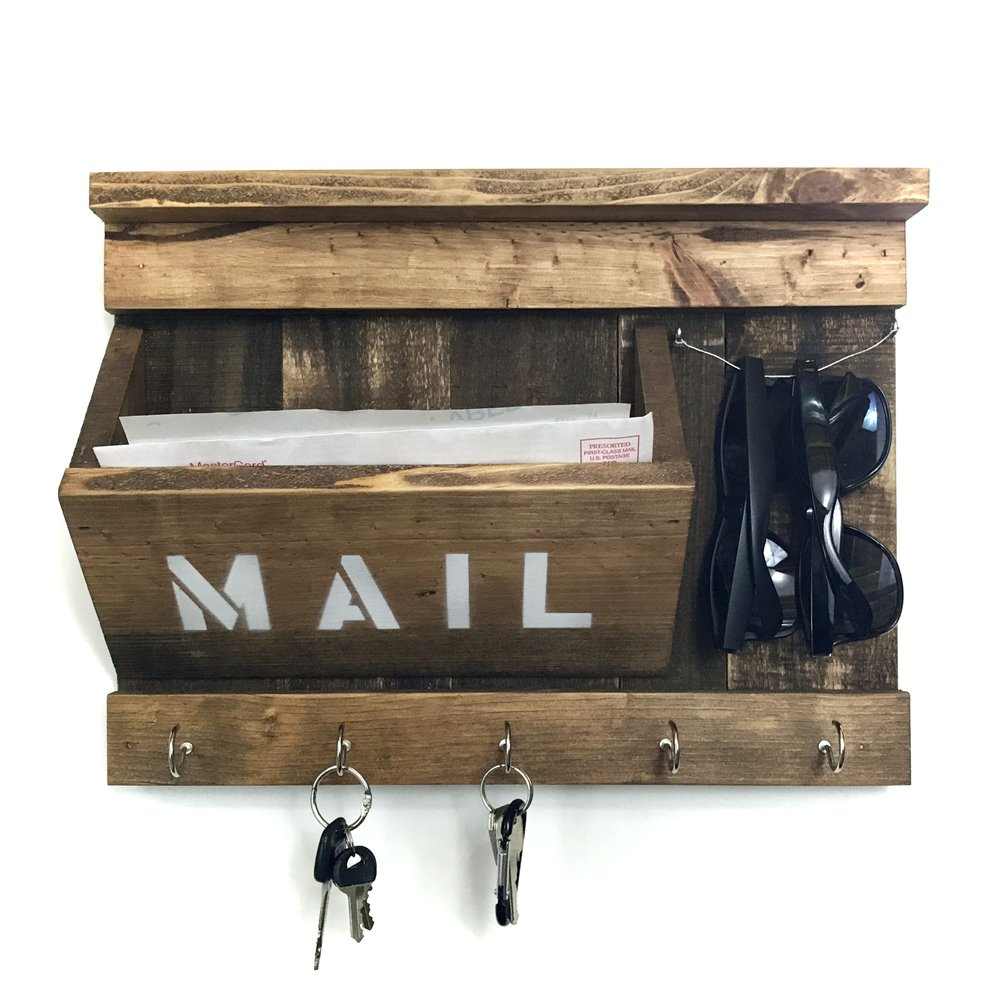 This one was an ode to the early design, utilizing new pine wood instead of reclaimed wood. I used large cup hooks for the key holders and spray painted the word mail using stencils, I colored the wood using Minwax Early American.