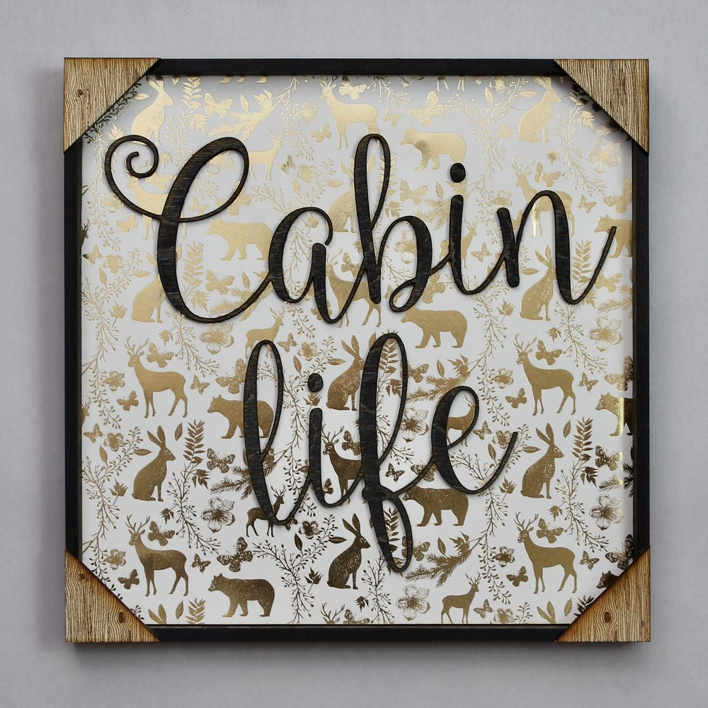 "I made this one for my Mom's cabin. I purchased the white and gold print from Michael's, the words were cut out of 1/8"" birch plywood and spray painted black, it is rounded out with a frame and some rustic corner pieces."