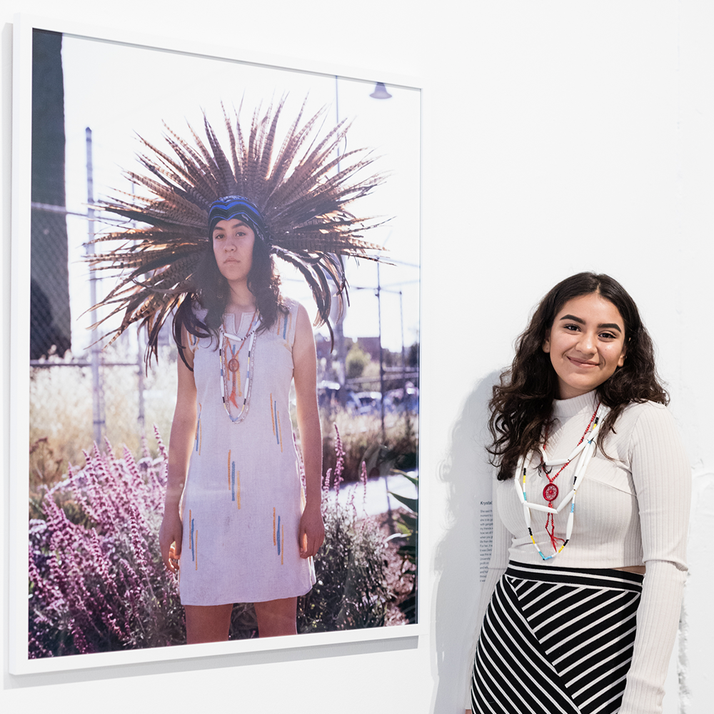 Krystal Escalante with her portrait taken by Star Montana, currently on view at Beta Main.