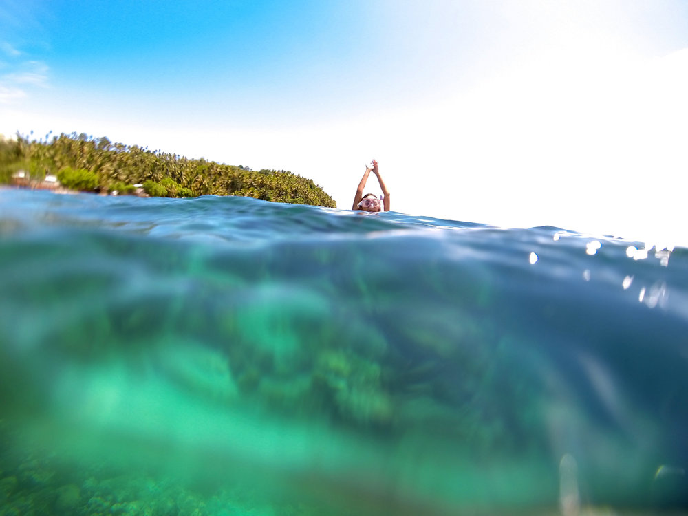 The clear waters surrounding Talicud Island make it one of the best places to go snorkeling. Here, an enthusiast is surfacing for air atop the shallow part of the reef after diving to a depth of around 10 feet.