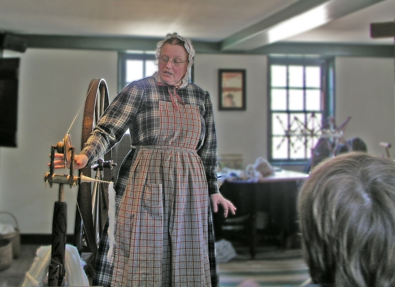 Above: A familiar scene: the spinning wheel demo. Sturbridge Village (photo by Rickpilot_2000, Flickr)