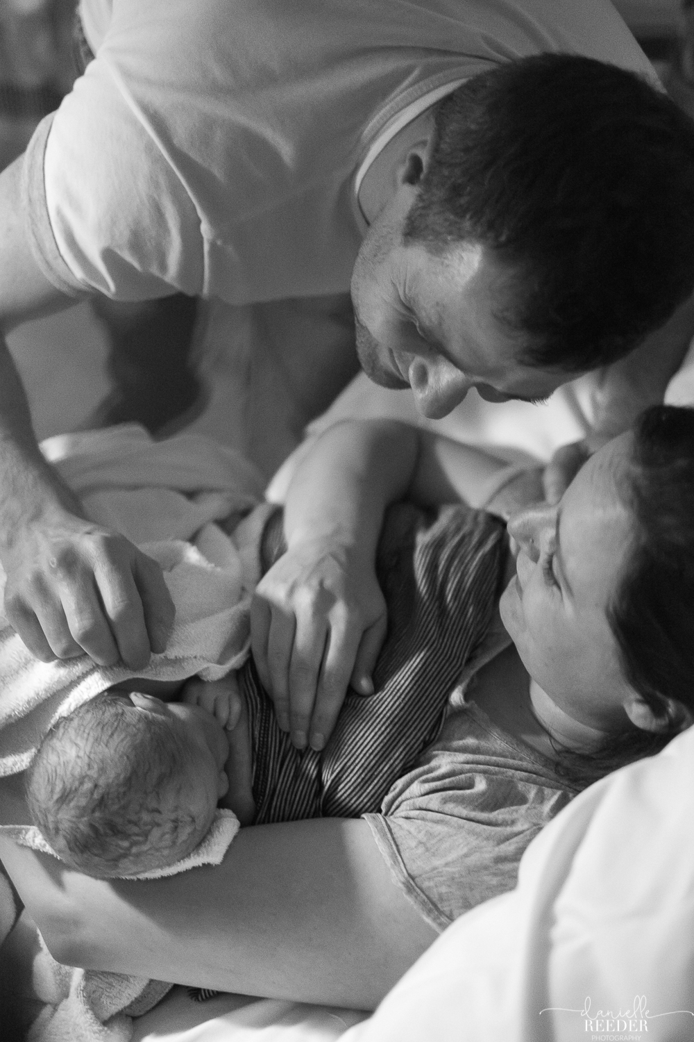 Daddy and mummy looking down at newborn daughter as she breatfeeds