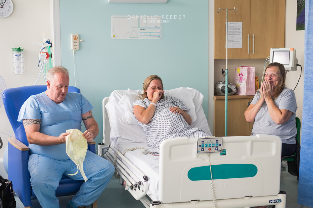 Expectant mama and her mum laughing at husband in hospital scrubs.
