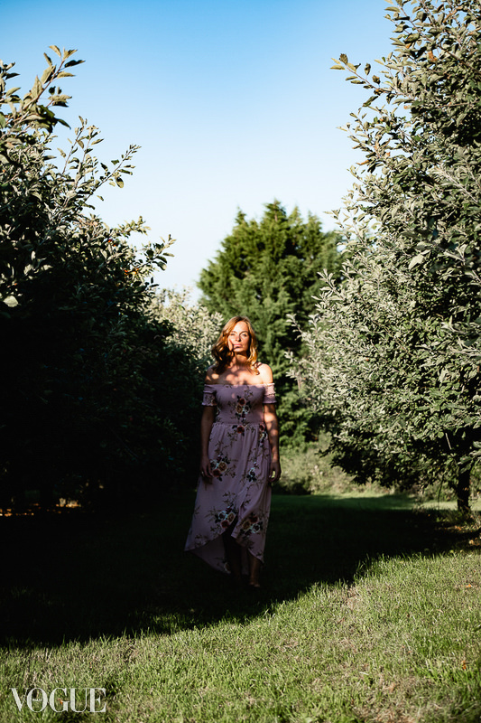 Woman walking throught the dappled light in a Somerset orchard. As featured on Vogue Italia
