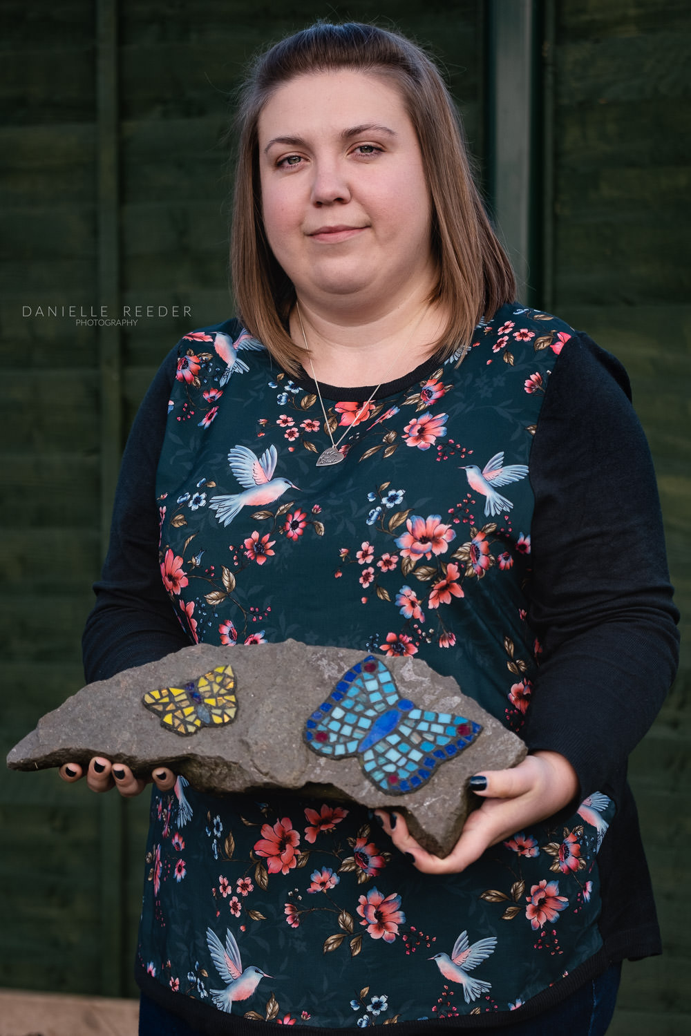 Portrait of a women stood holding a stone with two mosaic butterflies, each representing a baby lost in miscarriage.