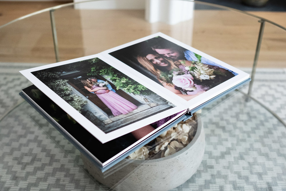 Photo album laying open on glass coffee table showcasing images inside.