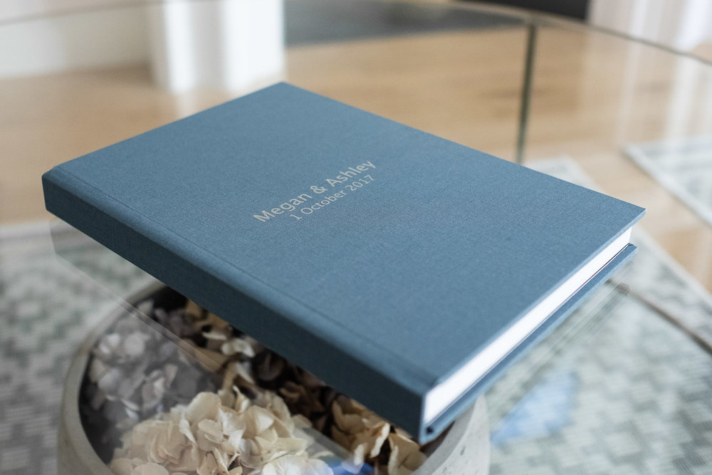 Blue linen covered photo album laying on a glass coffee table.