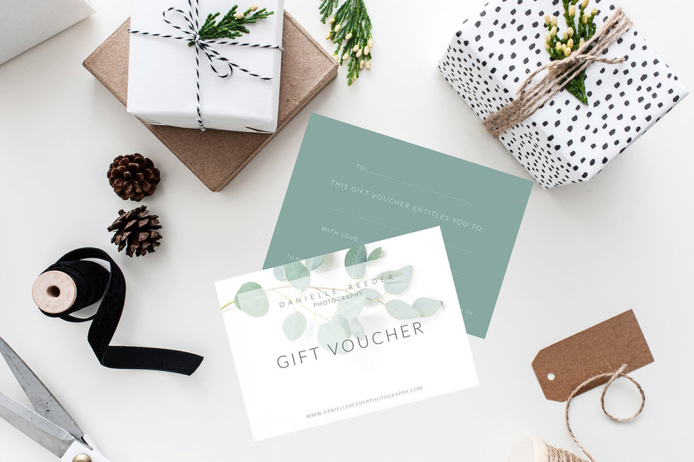 Presents wrapped in monochrome paper, tied with string and finished with green foliage. With gift vouchers laying next to them.